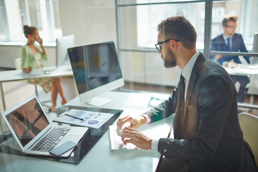 Young man working at two computer screens in office with coworkers in office nearby.